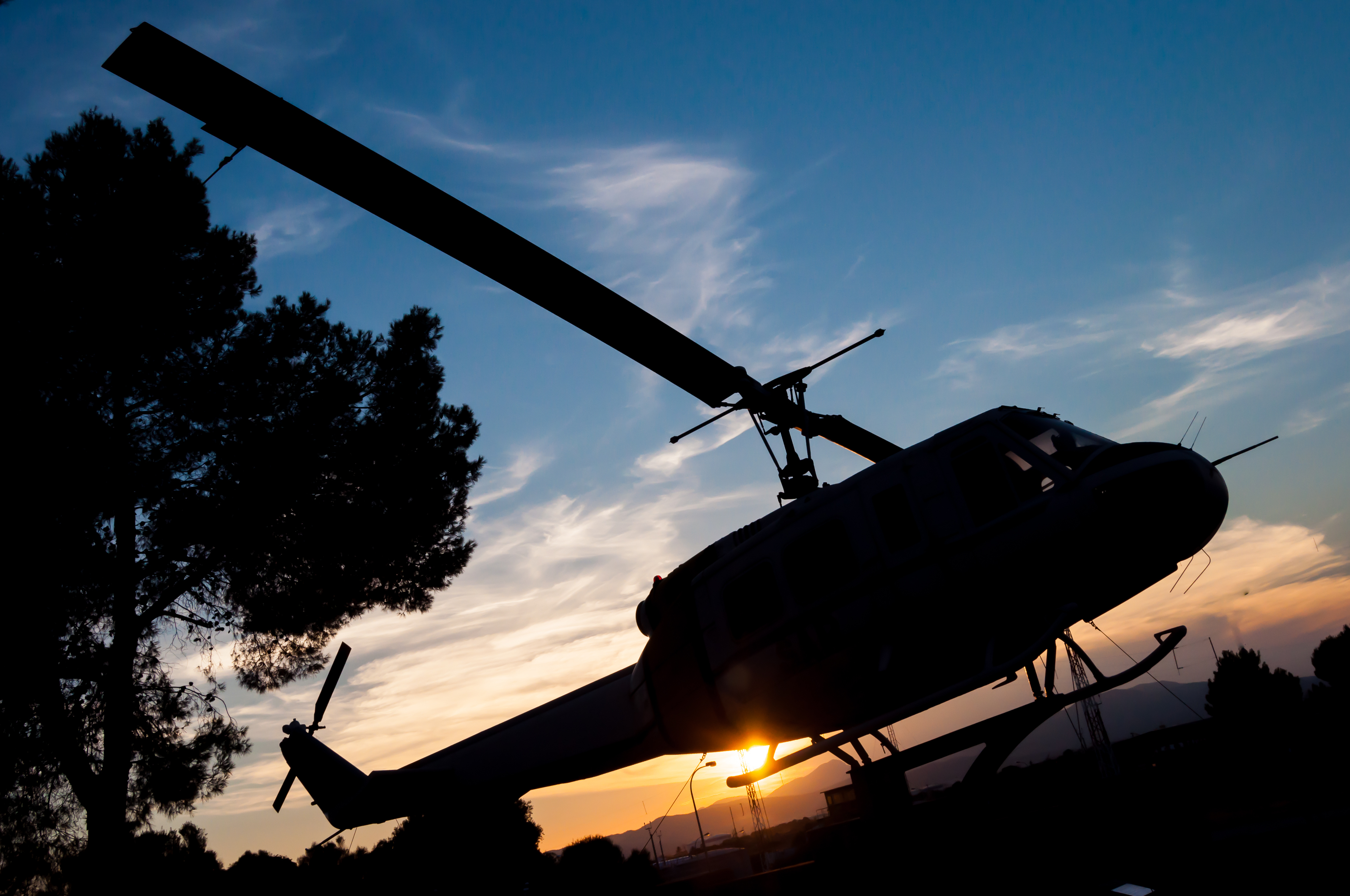 Silhouette of a helicopter on the backdrop of a sunset blue sky, representing aviation career opportunities with M&E